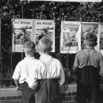 German boys view propaganda posters that are posted on a fence in Berlin
